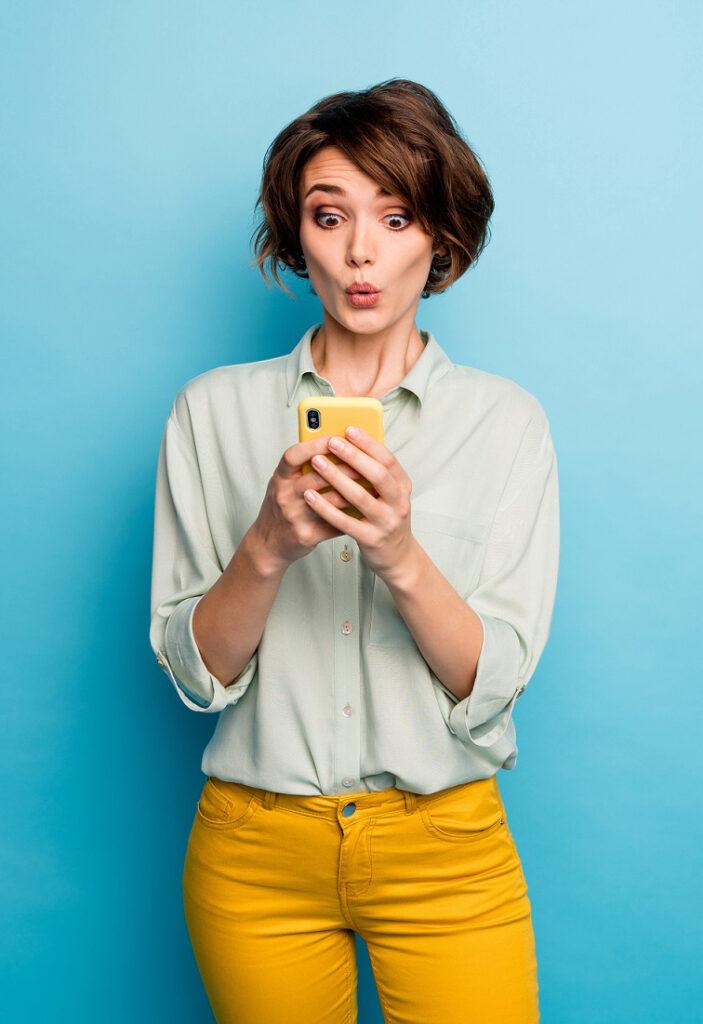 Frau ist überrascht während Blick auf Handy